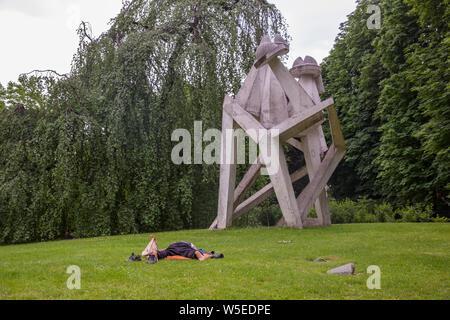 Sans-abri dans le Parco Sempione à Milan, à côté d'une sculpture. Banque D'Images