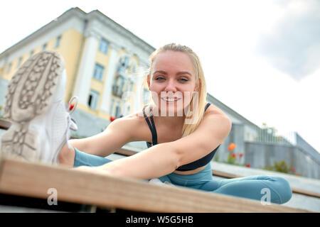 Belle jeune fille athlétique dans les vêtements de sport, faire des exercices d'étirement sur la rue, l'élément de la gymnastique, faire du béton se divise. Banque D'Images