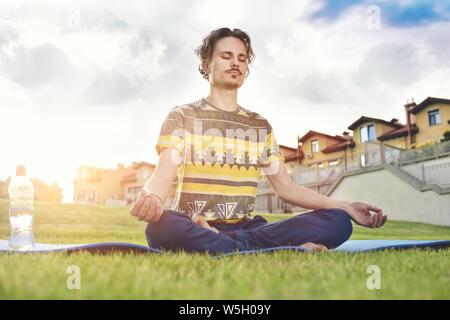 Jeune homme méditant à l'extérieur dans le parc, assis avec les yeux fermés et les mains Banque D'Images