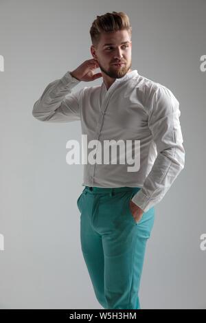 Curieux homme regardant par-dessus son épaule et posant avec une main sur son cou et l'autre dans sa poche tout en portant une chemise blanche et debout sur le gra Banque D'Images