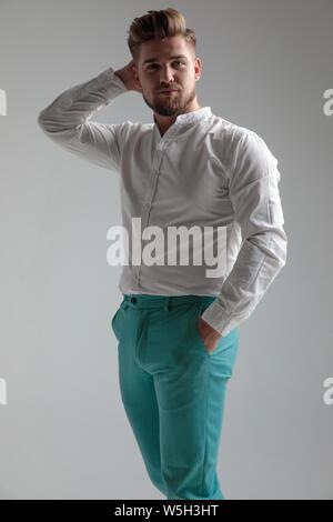 Beau Jeune homme posant détendu avec une main dans sa poche et l'autre sur son cou en portant des jeans et une chemise blanche, debout sur studio gris Banque D'Images