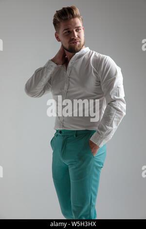 Homme confiant posing holding sa main sur son cou et dans sa poche tout en regardant par-dessus son épaule et portant une chemise blanche, debout sur studio gris Banque D'Images