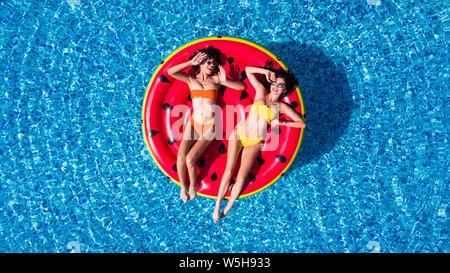 Vue aérienne de deux femmes flottant sur le matelas gonflable dans la piscine de détente
