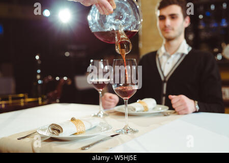 Waiter pouring red wine dans un verre dans un restaurant table. Banque D'Images