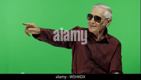 Man in sunglasses touristiques à points quelque chose. Beau vieil homme sur fond d'incrustation. Grand-père âgé en chemise marron. Place pour votre logo ou texte. Arrière-plan de l'écran vert Banque D'Images