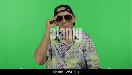 Man in sunglasses touristiques prêt pour les vacances. Beau vieil homme sur fond d'incrustation. Grand-père âgé en chemise colorée. Place pour votre logo ou texte. Arrière-plan de l'écran vert Banque D'Images