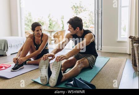 Couple exercising ensemble. L'homme et la femme dans Vêtements sports faisant d'entraînement à la maison. Banque D'Images