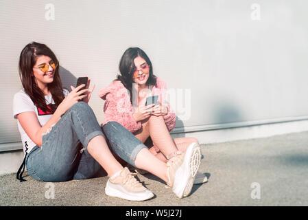 Deux belles jeunes femmes en utilisant leurs smartphones Banque D'Images