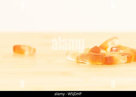 Un très léger et rêveur portrait de quelques bonbons en forme de bouteilles sur une table en bois. Les bonbons ont les mêmes couleurs que la moitié d'un flacon plein de cola. Banque D'Images