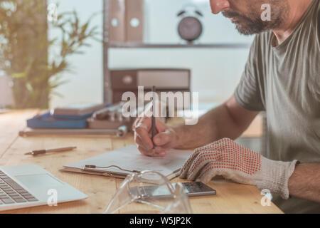 Projet de note dans la petite entreprise, l'atelier d'écriture de l'homme pour faire la liste au bureau