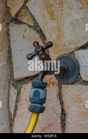 Un robinet ou robinet avec un tuyau jaune attaché pour l'arrosage du jardin. Banque D'Images