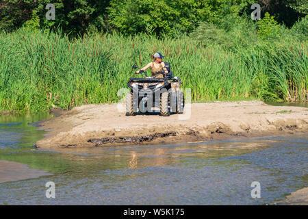 Une fille sur un quad à cheval sur la plage. Une femme heureuse équitation quad sur la rivière.