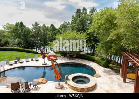 Piscine extérieure de luxe avec l'aménagement paysager, dans l'arrière-cour d'une maison, donnant sur le lac. Banque D'Images