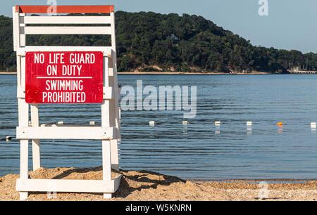 Un livre blanc de secours avec un panneau rouge lecture pas de vie garde la baignade est interdit, c'est debout sur le sable avec vue sur la baie, avec des collines en Banque D'Images