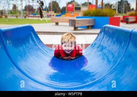 Un garçon de deux ans se couche une diapositive bleu sur le ventre, de s'amuser à un nouveau terrain, à Canterbury, Nouvelle-Zélande