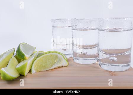 Close-up de tranches de citron empilés sur une planche à découper en bois et trois verres de tequila sur fond blanc - Tequila luxueux Banque D'Images