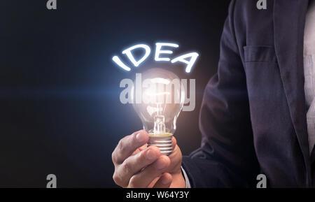 Young Woman in suit holding ampoule idée dans la main sur noir Banque D'Images