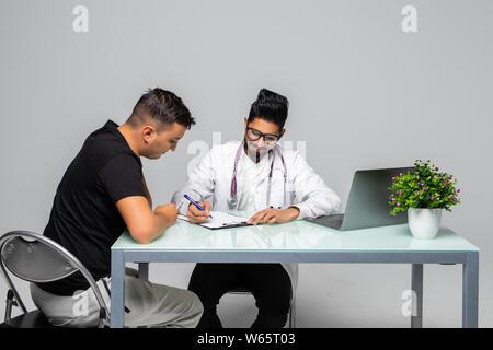 Médecin indien prescription pour patient assis au bureau bureau médical, isolé sur fond blanc