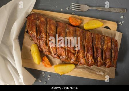 Côtes levées de porc mariné cuit au four avec des pommes de terre. Porc sur le BBQ. Installations pour Barbecue. Mise à plat. Banque D'Images