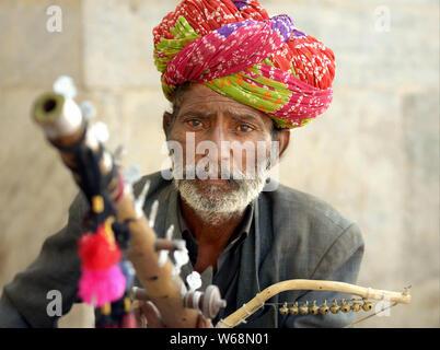 Rajsthani Indiennes âgées street musicien joue son ravanahatha traditionnels (instrument à cordes indien courbé). Banque D'Images