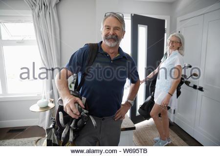 Portrait couple confiant avec des sacs de golf de quitter la maison Banque D'Images