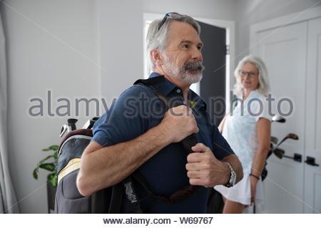 Happy senior couple avec des sacs de golf de quitter la maison Banque D'Images