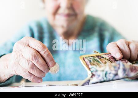 Photo gros plan détaillé de womans mains âgées méconnaissable restants de comptage de pièces dans son portefeuille de retraite après le paiement des factures.