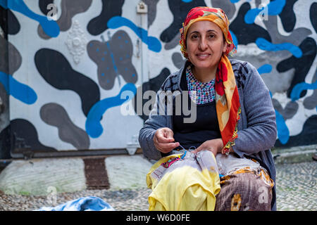 Portrait d'une femme turque dans un foulard la couture dans la rue en face de sa maison à Istanbul, Turquie Banque D'Images