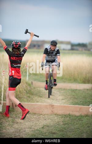 Abingdon, Oxfordshire, UK. 1 Août, 2019. Les enfants célébrer après un cycliste prend sur le défi de l'autre sur les planches. Prendre3 Série CX d'été. L'événement de cyclocross à l'aérodrome d'Abingdon les jeudis attire les cyclistes de 6 à 60 quelque chose. Course de vélo de cyclocross en terrain mixte.Le temps était chaud et partiellement nuageux. Credit: Sidney Bruere/Alamy Live News Banque D'Images