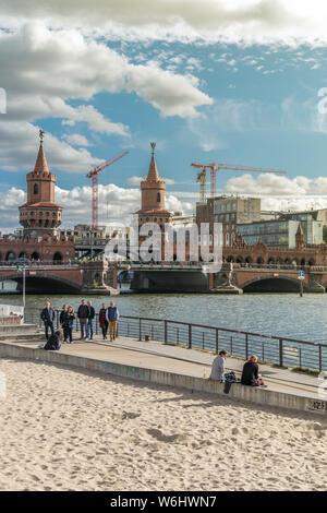 BERLIN, ALLEMAGNE - 26 septembre 2018: Panorama de Berlinois s'asseoir près de la rivière Spree, à proximité de l'East Side Gallery avec le Pont de l'Oberbaum Banque D'Images