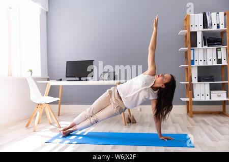 Young Businesswoman Doing Stretching exercice sur tapis d'exercice sur le lieu de travail Banque D'Images