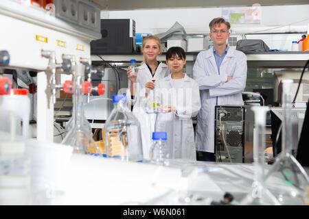 Des scientifiques, hommes et femmes en blouse blanche posant au laboratoire de biochimie Banque D'Images