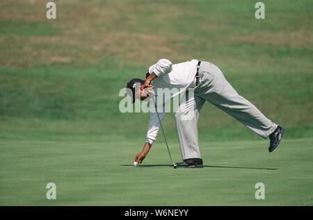Tiger Woods du USA remplacement sa balle de golf sur le green qu'il avait marquée d'une pièce de monnaie à 127e Open Championship 1998 majestueux, juillet, Royal B Banque D'Images