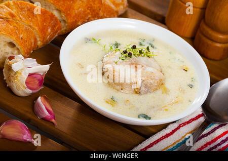 Soupe de morue délicieux dans un bol blanc avec baguette garnie de microgreens Banque D'Images