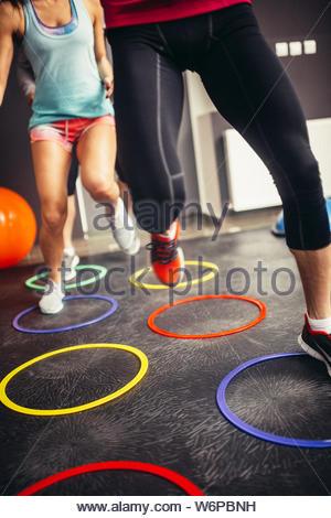Les gens dans la salle de sport fitness jumping over.anneaux effet Grain ajouté pour l'impression artistique. Banque D'Images