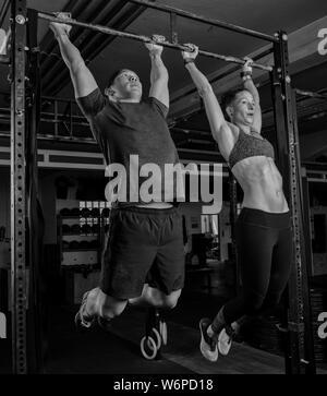 Un jeune couple d'athlétisme est en train de faire une formation de remise en forme et d'avoir du plaisir ensemble. Homme fort et la femme font l'exercice orteils pour bar.