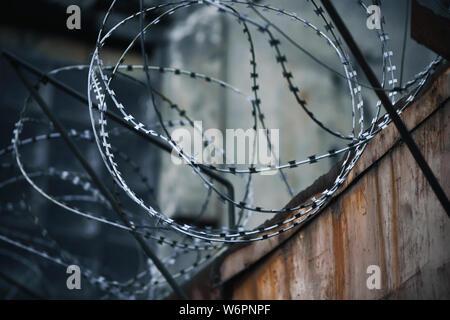 Sur une ancienne prison clôture rouillée enroulé sur le haut de la spirale metal sharp barbelés, créant une ambiance sombre et oppressante particulièrement