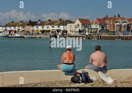 Un excès de couple assis sur le bord de l'eau. Littlehampton, West Sussex, England, UK Banque D'Images