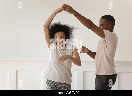 Happy young couple holding hands laughing dancing at home Banque D'Images
