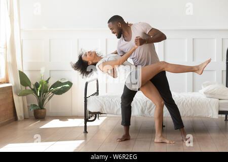 Romantique Active african american couple wearing pajamas danser dans la chambre Banque D'Images