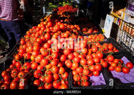 Tomates fraîches rouge vif sur un légumes dans le dynamique marché hebdomadaire le vendredi à Oliva en Espagne Banque D'Images