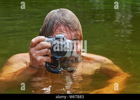 Homme barbu d'âge mûr avec un appareil photo imperméable dans ses mains fait des photos au cours de la nage dans la rivière.