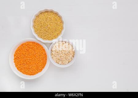Différents types de lentilles, céréales et flocons boulgour chêne sur fond blanc télévision jeter Vue supérieure avec copie espace. Banque D'Images