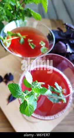 Vue de dessus de deux verres avec un cocktail rafraîchissant rouge décoré de feuilles de menthe sur fond de bouquets de menthe et basilic pourpre, selective focus