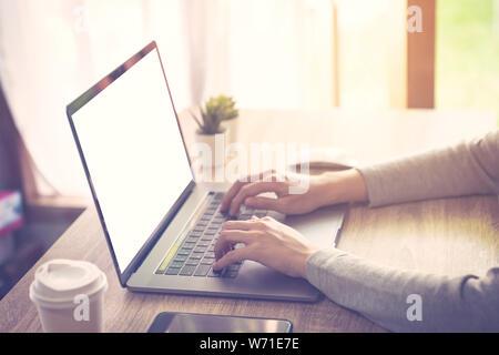 Business Woman using laptop computer n'activité en ligne sur table en bois au bureau à domicile.
