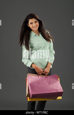 Woman carrying shopping bags et pointant vers la caméra Banque D'Images