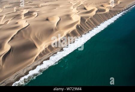 Vue aérienne de la côte des squelettes des dunes de répondre aux vagues d'Atlanic ocean. Skeleton Coast, Namibie. Banque D'Images
