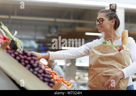 Vue de côté portrait de jeune femme contemporaine en choisissant des fruits à farmers market, copy space Banque D'Images