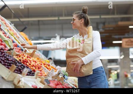 Taille portrait de jeune femme contemporaine en choisissant des fruits à farmers market, copy space Banque D'Images