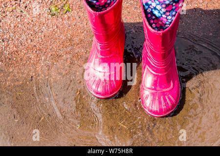 Les jambes de l'enfant dans les bottes en caoutchouc orange sautant dans les flaques d'automne. Enfants bottes en caoutchouc lumineux,le jardinage. Rainy day fashion.chaussures en caoutchouc pluie Jardin Banque D'Images